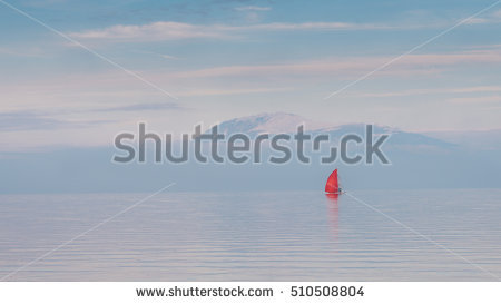 stock-photo-red-sail-boat-in-lake-garda-italy-during-the-winter-510508804