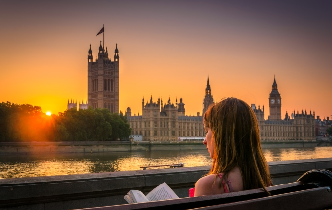 Woman reading book next to Houses of Parliament, London