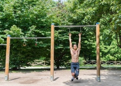 Young athletic shirtless man exercising on monkey bars in a park