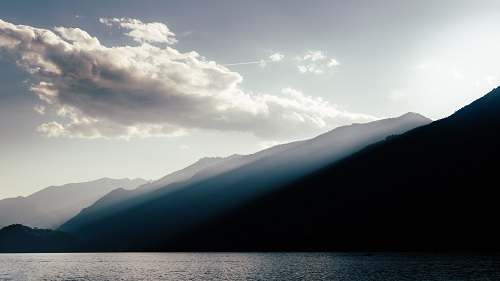 Clouds casting god rays on a diffused silhouette of Lake Como, Italy