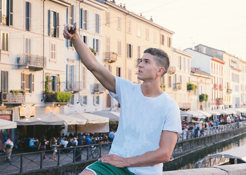 """Handsome young man outdoors taking photo or """"selfie"""" with cell phone's camera, in bohemian Navigli area of Milan, Italy"""