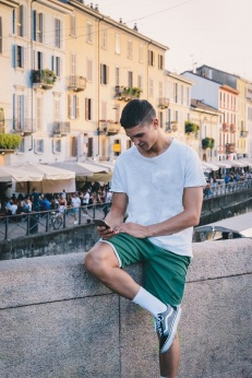 "Handsome young man outdoors taking photo or ""selfie"" with cell phone's camera, in bohemian Navigli area of Milan, Italy"