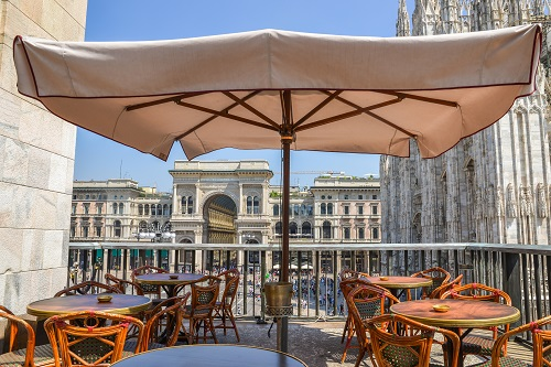 A drinks balcony overlooking Piazza Duomo in Milan, Italy on a summer day