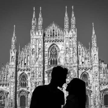 Silhouette of a young couple kiss in front of Milan' s Gothic cathedral