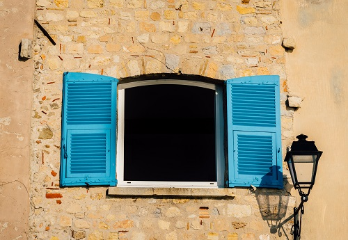 Bright blue shutters with a lamp post on a rustic wall in Provence, France