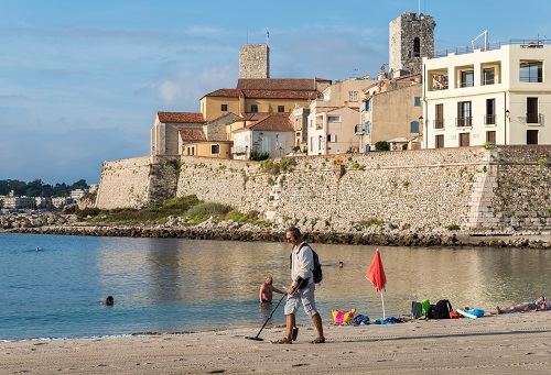 A man uses a metal detector on a beach overlooking Antibes, Cote d'Azur, France