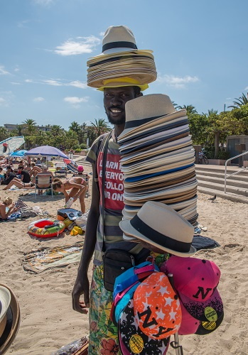 An African man sells straw hats on the beach in Antibes, France