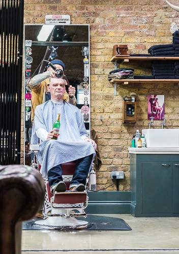 Hipster man drinking a beer having his hair cut in Shoreditch, London, England