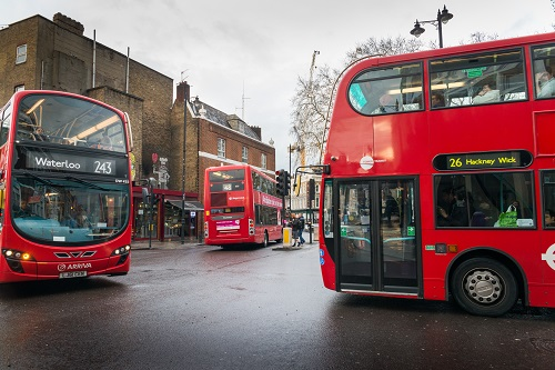 Three red London, England buses in an intersection