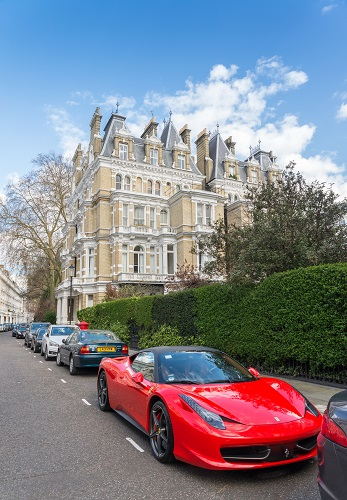 A red ferrari parked on a Kensington & Chelsea Borough, London, UK street