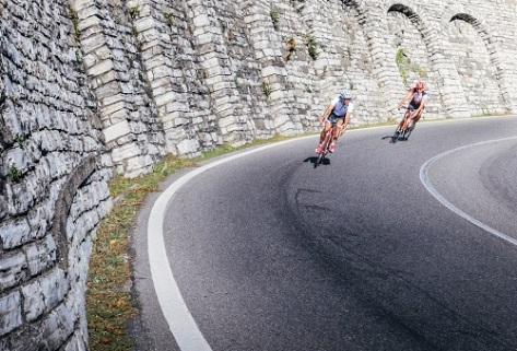 Two high-speed cyclists ride downhill on a curve in Como, Italy