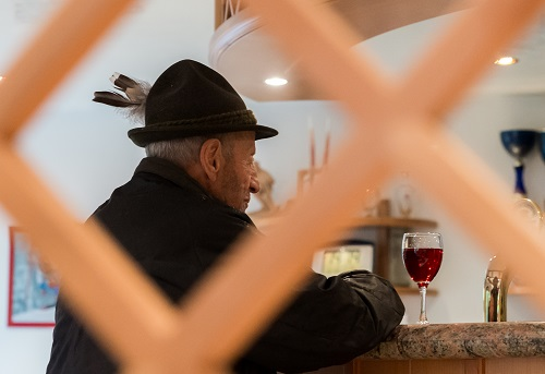Old man with typical Austrian clothes drinks a red wine at a bar