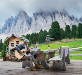 Young well-dressed man (30-35) playing a guitar with Italian Dolomites rock formation background