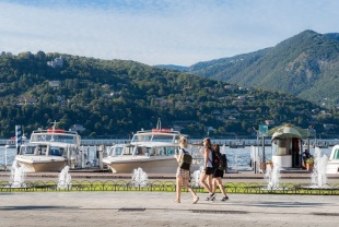 Young tourist women enjoy a stroll and gelato alongside Como on Lake Como, Italy