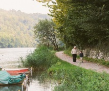 Grandfather and grandson hold hands while walking on a path next to a river in Italy