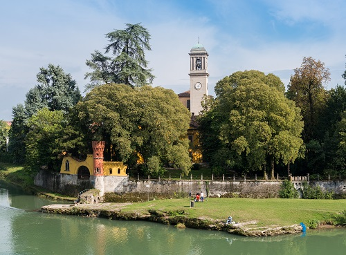 Fishermen relax next to a churchtower in Cassano d'Adda, Italy