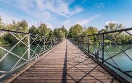 Diminishing perspective pedestrian bridge crossing River Adda in Italy