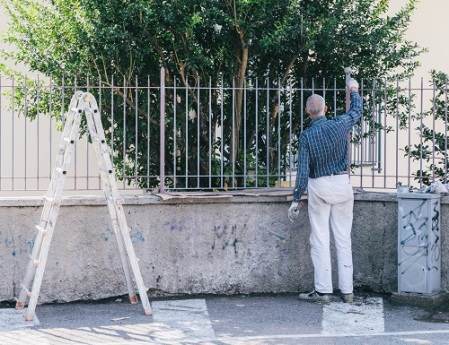 Older man painting a fence