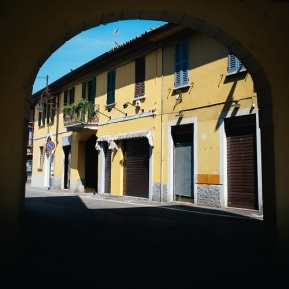 Archway to a street with traditional shops in Italy