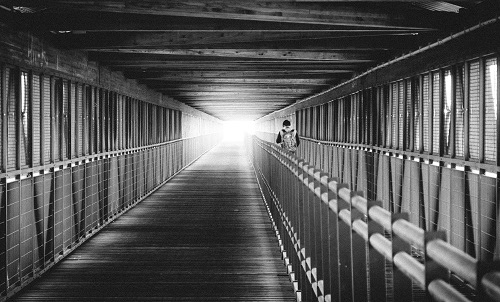 Young man walks towards a light at the end of a pedestrian tunnel