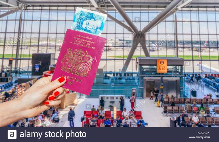 hand-holding-uk-passport-and-uk-5-pound-note-with-busy-airport-waiting-KDCACX