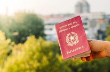 Someone holding an Italian passport with an urban background. Italy is part of the European Union