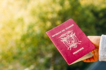 Someone holding a passport from the Republic of Ecuador, isolated. Ecuador is in South America