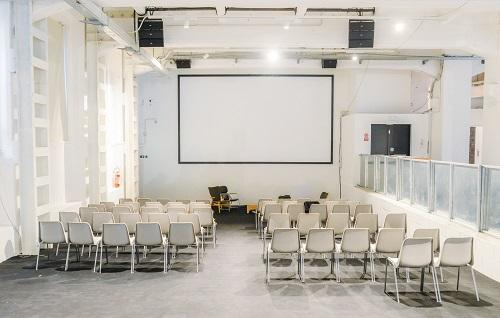 Empty and brightly lit presentation room with chairs and projector