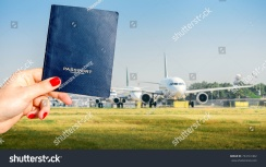 stock-photo-digital-composite-of-holding-a-generic-passport-with-a-row-of-commercial-airplanes-on-taxiing-on-734161402