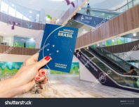 stock-photo-hand-holding-a-brazilian-passport-inside-a-brightly-lit-airport-terminal-733739728