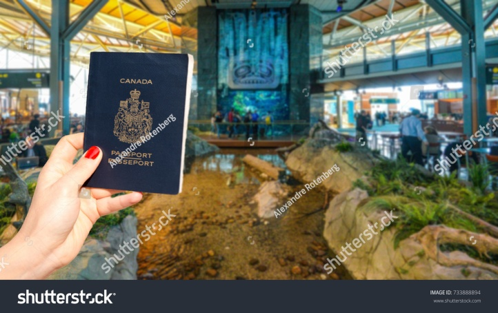stock-photo-hand-holding-a-canadian-passport-at-vancouver-international-airport-lounge-733888894