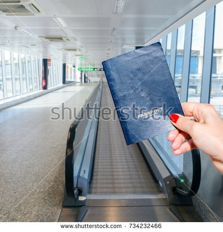 stock-photo-hand-holding-a-generic-passport-at-airport-terminal-734232466