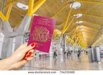 stock-photo-hand-holding-uk-passport-just-before-boarding-734235568