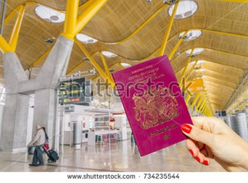 stock-photo-hand-holding-uk-passport-just-before-boarding-three-different-lines-group-group-and-group-734235544