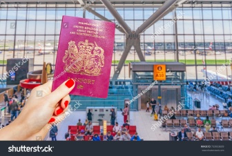 stock-photo-hand-holding-uk-passport-with-busy-airport-waiting-lounge-and-airplanes-in-background-733933609