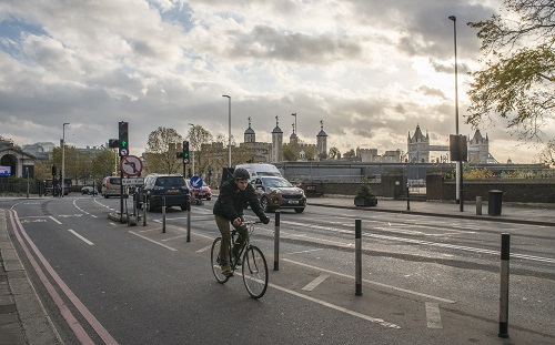 Cyclist on segregated cycling lane near Tower Hill in the City of London, UK