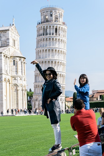 Asian tourists take pictures of the Leaning Tower of Pisa with arms raised using their smartphones, Pisa, Tuscany, Italy