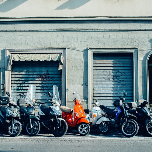 Red Italian vespa parked on street with other motorbikes