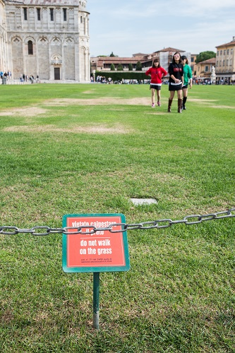 Asian tourists in Pisa, Italy disobey the sign to keep off the grass