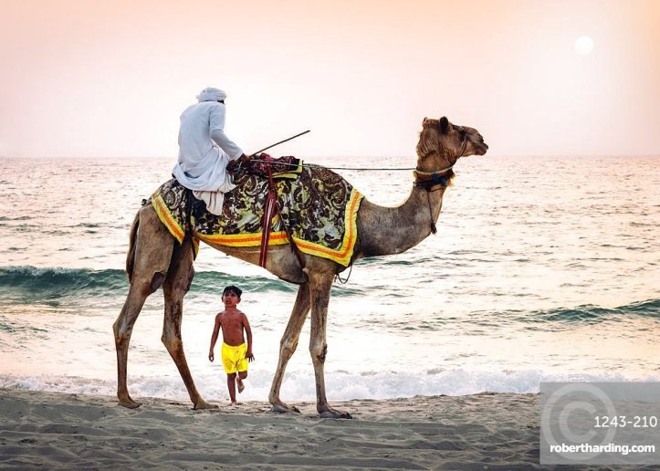 Boy stares in amazement at Arabic man wearing a thawb riding a camel on a beach, Dubai, UAE