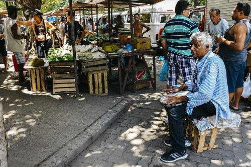 Older Brazilian man playing drums in a street market in Rio de Janeiro, Brazil