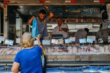 Customer purchases fish at a market in Rio de Janeiro, Brazil
