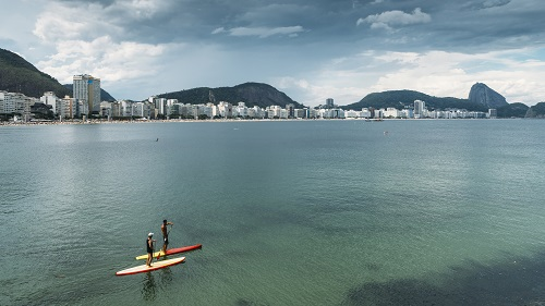 Pure wanderlust as two men on a Stand Up Paddle on Copacabana Be