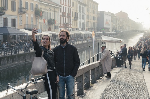 A couple take a selfie picture at Milan, Italy's Navigli Grande