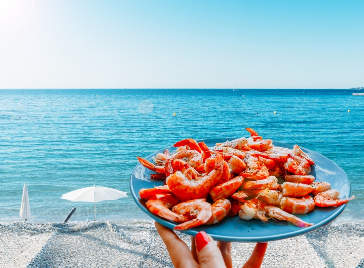 Prawns or shrimp on a plate at edge of beautiful Mediterranean beach