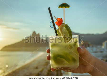 stock-photo-caipirinha-cocktail-with-a-kiwi-twist-with-rio-de-janeiro-brazil-beach-background-413642626