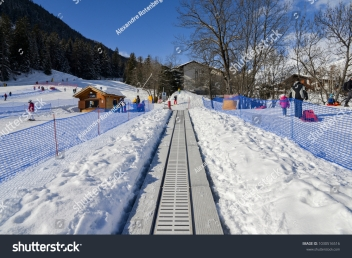 stock-photo-la-thuile-italy-feb-ascending-conveyor-belt-to-a-beginners-run-for-children-and-1030516516