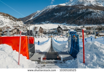 stock-photo-la-thuile-italy-feb-ascending-conveyor-belt-to-a-beginners-run-for-children-and-1030516525
