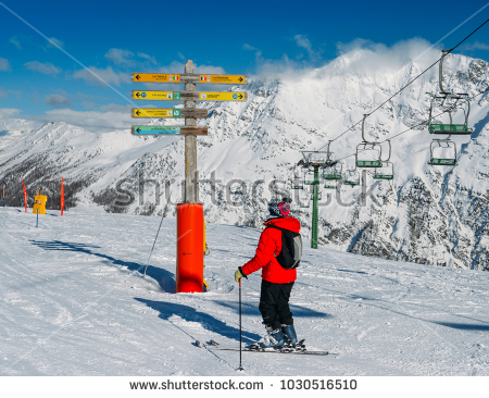 stock-photo-la-thuile-italy-feb-skier-looking-at-signpost-in-the-ski-resort-of-la-thuile-1030516510