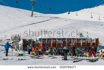 stock-photo-la-thuile-italy-feb-skiers-and-snowboarders-with-their-gear-relax-at-a-wooden-cabin-at-1030768477
